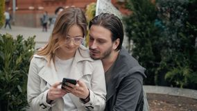 Cute young beautiful couple sitting on the ground in city near university after studying and having fun together. Laughing and smiling stock footage