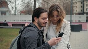 Cute young beautiful couple sitting on the ground in city near university after studying and having fun together. Laughing and smiling stock video footage