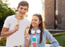 Cute young beautiful teen couple with ice cream. Cute young beautiful teen couple in city near university with ice cream after studying and having fun together Royalty Free Stock Photography