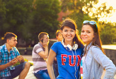 Cute young beautiful teens sitting in city near university after. Studying and having fun together laughing and smiling Stock Photography