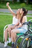 Cute young biker women taking self portrait in park Stock Photo