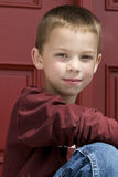 Cute young blond boy. 6 year old blond boy with green eyes.  tight shot with red door in background Stock Photo