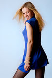 Cute young blond girl in blue dress. On a blue background Royalty Free Stock Photography