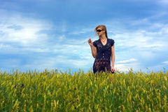 Cute young blond girl on a field in summer. Blue sky purple dress Stock Photos