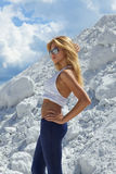 Cute young blond girl in white shirt and blue. Pants, white mountains Stock Photo