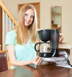 Cute young blond with new  coffee maker at the table Royalty Free Stock Image