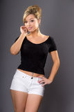 Cute young blonde model, posing in white shorts and dark top Stock Photos