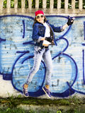 Cute young blonde teenager girl in a baseball cap and jeans shirt jumping against a stone wall background. Hip hop,. Dancing Royalty Free Stock Images