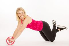 Cute young blonde woman doing sports exercises. On white background Royalty Free Stock Photography
