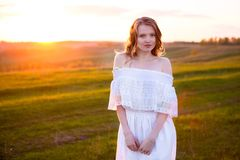 Cute young blonde woman in green field at summer or spring sunset royalty free stock photo