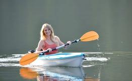 Cute young blonde woman - kayaking at lake Stock Image