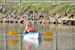 Cute young blonde woman - kayaking at lake Stock Images
