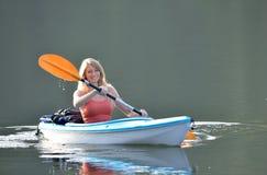 Cute young blonde woman - kayaking at lake Royalty Free Stock Photos