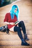 Cute young blue-haired grunge rock girl sitting on stairs and reading a book. Cute young blue-haired grunge rock girl sitting on stairs and reading book royalty free stock photos