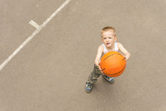 Cute young boy aiming the basketball at the net Stock Images