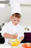 Cute young boy baking a cake Royalty Free Stock Photo
