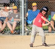 Little Boy with eyes on the ball League Baseball. Cute little boy at bat in a baseball game ready to hit the ball that is in view Royalty Free Stock Photos