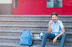 Cute, young boy in blue shirt with backpack holds globe in his hands on the steps in front of his school. Education stock photos