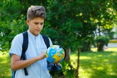 Cute, young boy in blue shirt with backpack holds globe and point on it. Education, back to school royalty free stock photography