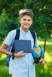 Cute, young boy in blue shirt holds a globe in his arms in the park in the summer. Back to school, education concept. Beginning of the school year stock images