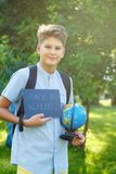 Cute, young boy in blue shirt holds a globe in his arms in the park in the summer. Back to school, education concept. Beginning of the school year royalty free stock images