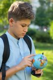 Cute, young boy in blue shirt holds a globe in his arms in the park in the summer. Back to school, education concept stock photo