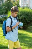 Cute, young boy in blue shirt holds a globe in his arms in the park in the summer. Back to school, education concept. Beginning of the school year stock image