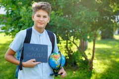 Cute, young boy in blue shirt holds a globe in his arms in the park in the summer. Back to school, education concept. Beginning of the school year royalty free stock photography