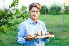 Cute, young boy in blue shirt and round glasses plays on the wooden chessboard on the grass in the park. Education, hobby, stock image
