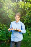 Cute, young boy in blue shirt and round glasses plays on the wooden chessboard on the grass in the park. Education, hobby, stock photography