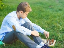 Cute, young boy in blue shirt and round glasses plays on the wooden chessboard on the grass in the park. Education, hobby, stock photo