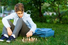 Cute, young boy in blue shirt and round glasses plays on the wooden chessboard on the grass in the park. Education, hobby stock image