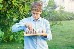 Cute, young boy in blue shirt and round glasses plays on the wooden chessboard on the grass in the park. Education, hobby, royalty free stock images