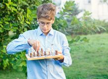 Cute, young boy in blue shirt and round glasses plays on the wooden chessboard on the grass in the park. Education, hobby, stock images