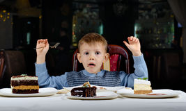 Cute young boy celebrating his birthday. Line different cake front him pulling comic face  tries make his mind where begin eating Royalty Free Stock Photography