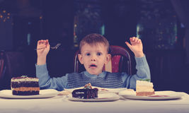 Cute young boy celebrating his birthday. Line up  different cake front of him pulling comic face tries make mind where begin eating Royalty Free Stock Photo