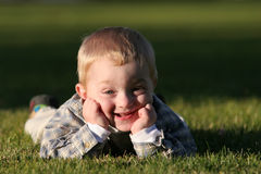 Cute young boy with cheeky grin. Cute young boy with cheeky, silly grin laying in the grass stock photography