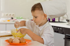 Cute young boy chef whipping the eggs Royalty Free Stock Images