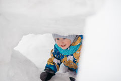 Cute young boy child is playing outside in igloo fort tunnel he dug in pile of snow on winter day. Royalty Free Stock Photos