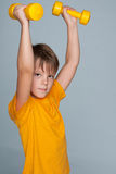 Cute young boy with dumbbells Royalty Free Stock Photos
