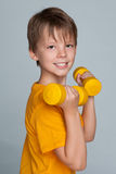 Cute young boy with dumbbells do exercises Stock Photos
