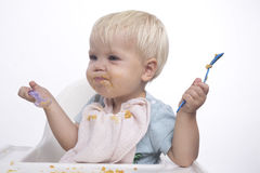 Cute young boy eating with messy face. Cute young boy feeding himself with messy face, white background Stock Photo