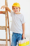 Cute young boy, foreman standing near the ladder Stock Image