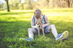 Cute, young boy in the garden holding a boxer dog. A Cute, young boy in the garden holding a boxer dog Royalty Free Stock Photography