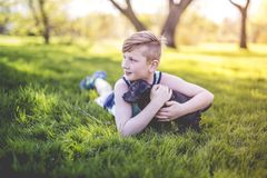 Cute, young boy in the garden holding a boxer dog Royalty Free Stock Images