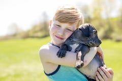Cute, young boy in the garden holding a boxer dog Royalty Free Stock Photos