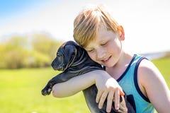 Cute, young boy in the garden holding a boxer dog. A Cute, young boy in the garden holding a boxer dog Stock Photo