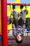 Cute young boy hanging upside down on a playground royalty free stock photography