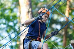 Cute young boy in helmet with climbing equipment in the rope amusement park. Summer camp stock image