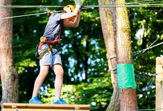 Cute young boy in helmet with climbing equipment in the rope amusement park. Summer camp, holidays. Concept stock image